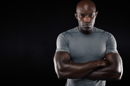 Studio portrait of a handsome young man in sportswear with his arms crossed standing against black background with copy space. Muscular african sportsman. Stock Photo