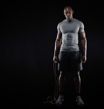 completo: Estudio tirado de ajuste y hombre muscular con la cuerda de salto de pie sobre fondo negro. Modelo afro americanos hombres con copyspace. Deportes y el concepto de fitness. Foto de archivo
