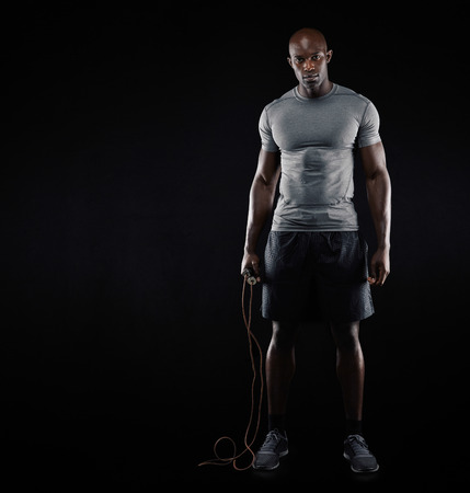 jump rope: Studio shot of fit and muscular man with jumping rope standing on black background. Afro american male model with copyspace. Sports and fitness concept. Stock Photo