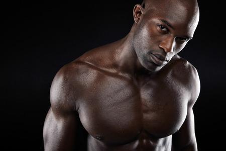 hombre sin camisa: Cierre plano de la imagen de hombre joven con estructura muscular. Modelo masculino descamisado africano con que mira la cámara sobre fondo negro.
