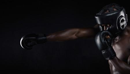 アフリカの男性ボクサー ボクシングの背景に黒のイメージ。青年保護ヘッド ガードとの戦いのための練習ボクシング グローブを着用します。
