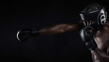 Image of african male boxer boxing against black background. Young man wearing protective head guard and boxing gloves practicing for fight.