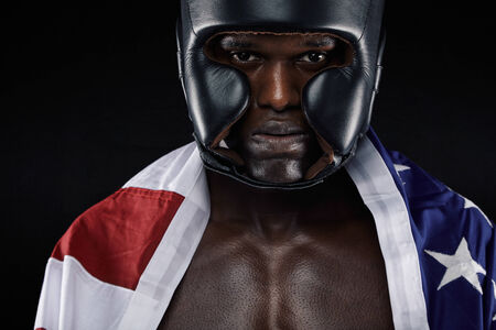Close-up portrait of young male wearing boxing helmet with american flag against black background photo