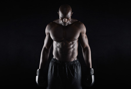 boxer shorts: Portrait of fit young man wearing boxing gloves looking down on black background. Professional african boxer.