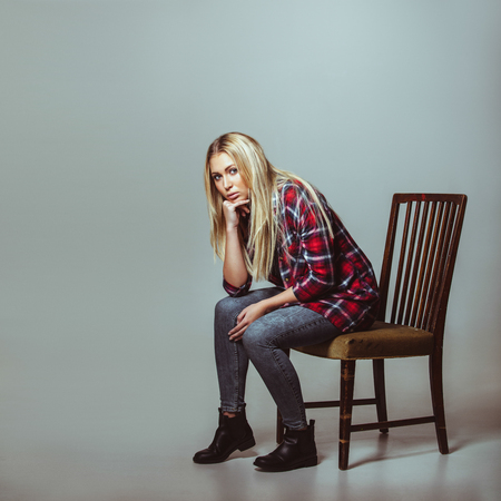 Studio shot of young woman in casual outfit sitting on chair looking at camera. Caucasian female model with copyspace. photo