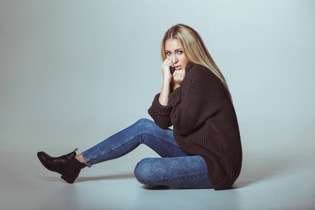 woman sweater: Portrait of attractive woman wearing sweater sitting on floor. Teenage girl looking at camera.