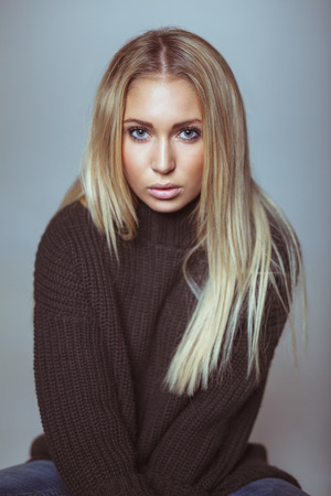 Portrait of beautiful young blond woman in sweater looking at camera. Caucasian female model against white wall. photo