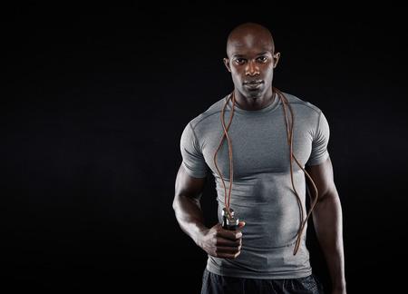 검은 배경에 밧줄을 점프 잘 생긴 근육 남자. 복사 공간이 많은 맞춤 아프리카 모델. 스톡 콘텐츠