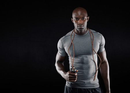 fit man: Handsome muscular man with jumping rope on black background. Fit african model with lots of copy space.