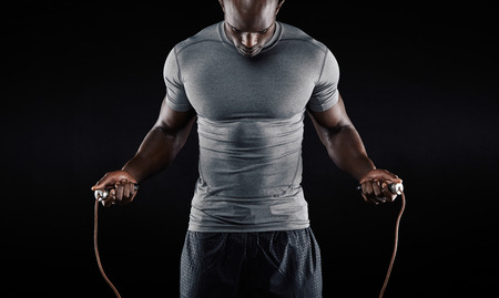 hombres haciendo ejercicio: Muscular hombre saltar la cuerda. Retrato de hombre joven y musculoso ejercicio con saltar la cuerda en el fondo negro