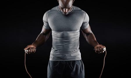 Svalnatý muž švihadlo. Portrét svalnatý mladík cvičení s skákání přes švihadlo na černém pozadí