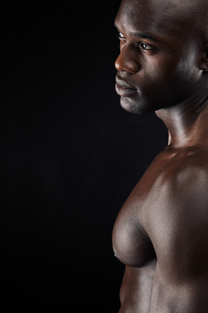 muscular build: Cropped shot of a man standing shirtless in the studio. African male model with muscular build on black background