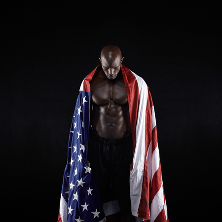 Male athlete carrying an American flag against black background. Studio shot of muscular sportsman with USA flag. Young man wrapped in flag. Stock Photo - 34577983
