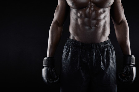 Closeup image of torso of young african male boxer wearing boxing gloves and shorts against black background Imagens
