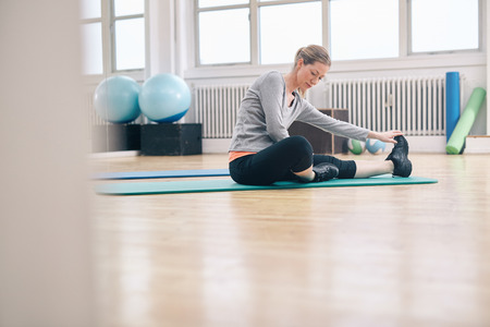 gym floor: Shot of an attractive woman sitting on the floor doing exercise. Fit woman sitting on exercise mate doing stretching workout. Stock Photo