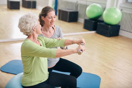 personas sentadas: Mujer mayor que ejercita con pesas en el gimnasio asistido por un entrenador de mujer joven. Anciana levantar pesas con la ayuda de un entrenador personal en rehabilitaci�n.