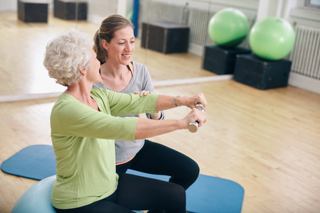 elderly: Senior woman exercising with weights in the gym assisted by a young female trainer. Old woman lifting dumbbells with help from personal trainer at rehab.