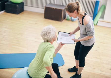 Senior woman in a gym sitting on exercise ball and talking to her private trainer about exercise plan