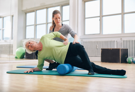 Female instructor helping senior woman using a foam roller for a myofascial release massage at gym. Banque d'images