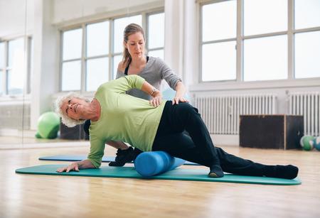 concepto equilibrio: Instructor de sexo femenino que ayuda mujer mayor con un rodillo de espuma para un masaje de liberaci�n miofascial en el gimnasio.