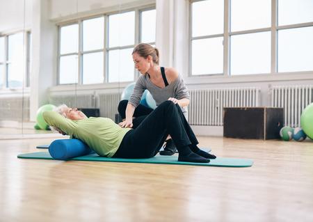 Senior femme effectuer les exercices du dos sur un rouleau de mousse étant assistée par son entraîneur personnel au gymnase. Physiothérapeute aider femme âgée à la réadaptation.
