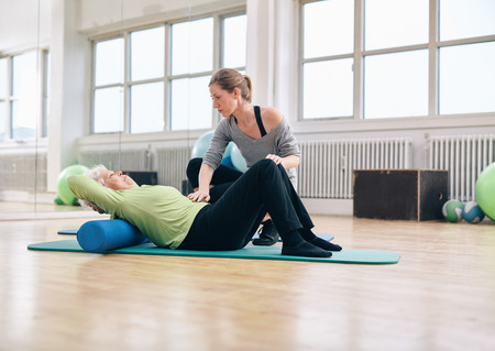 Senior woman performing back exercise on a foam roller being assisted by her personal trainer at gym. Physical therapist helping elder woman at rehab. Stock Photo