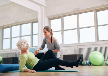 levantandose: Entrenador Ayuda femenina anciana levantarse de una estera de ejercicio en el gimnasio. Mujer mayor que es asistido por el instructor personal en rehabilitaci�n. Foto de archivo