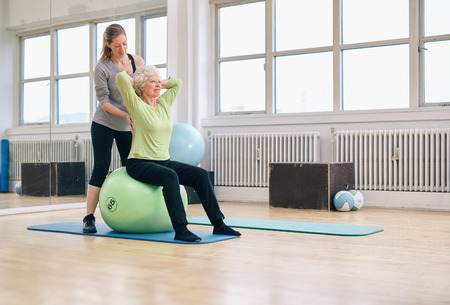 instructors: Senior woman sitting on a pilates ball  exercising at health club being assisted by her personal trainer. Physical therapist helping senior woman in her workout at gym.