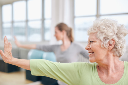 ヨガのクラスで伸張は試しにやって高齢者の女性のクローズ アップ ショット。フィットネス センターでのヨガの練習の女性。