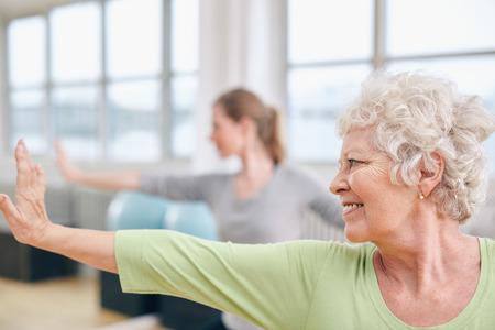 요가 클래스에서 스트레칭 운동을 하 고 할머니의 근접 쐈 어. 건강 클럽에서 요가 연습하는 여자.