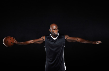 Portrait of muscular young man in sportswear holding a basketball standing with his arms outstretched looking away against black background.