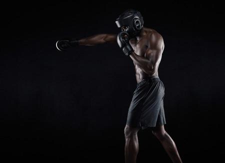 boxer: Vista lateral del hombre muscular de boxeo en el fondo negro. Afro var�n joven boxeador practicando boxeo de sombra americano.