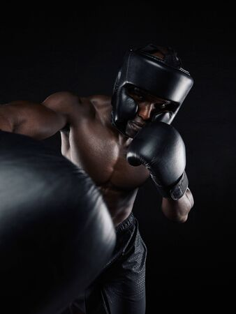 boxing gloves: Portrait of a young man boxer throwing a punch at camera while practicing on black background. Male athlete wearing boxing gloves exercising boxing. Stock Photo