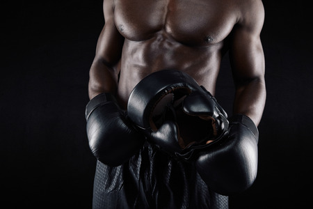 arts backgrounds: Cropped image of muscular young man wearing boxing gloves holding head protective helmet against black background. African male boxer relaxing after workout.