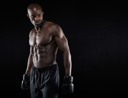 Shirtless african boxer looking away on black background. Young man wearing boxing gloves looking at copy space. Imagens