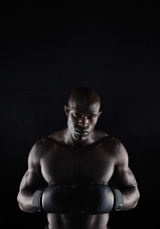 stance: Portrait of professional male boxer against black background. Strong and muscular young man in boxing gear.