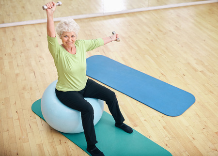 Active senior woman sitting on a pilates ball and lifting dumbbells looking at camera. Old caucasian woman exercising with weights at gym. Stock Photo