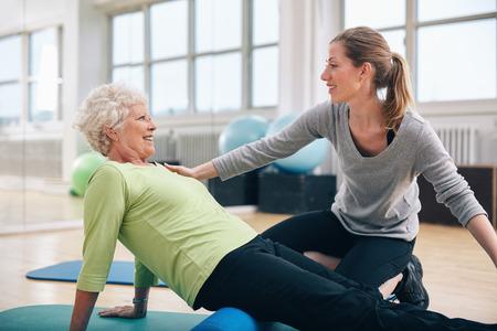 Sjukgymnast som arbetar med en äldre kvinna på rehab. Kvinnlig tränare hjälpa äldre kvinna gör övningen på skumgummirulle på gymmet. Stockfoto