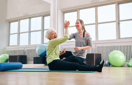 health conscious: Senior woman sitting on fitness mat giving high five to her personal trainer at gym. Excited old woman rejoicing health success with her instructor at rehab. Stock Photo