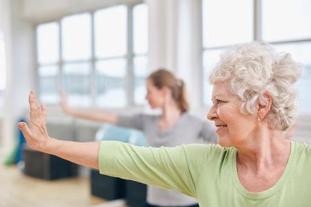 Indoor shot van senior vrouw doen stretching oefening op yogales. Vrouwen beoefenen van yoga op gymnasium.