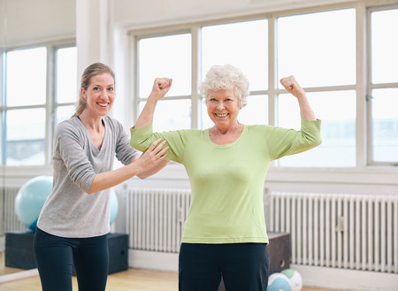 Portrait of a fit old woman flexing her arms and showing her muscles with personal trainer at gym