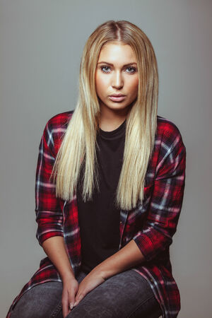 Portrait of beautiful young blond woman in casual outfit. Attractive female fashion model looking at camera. photo