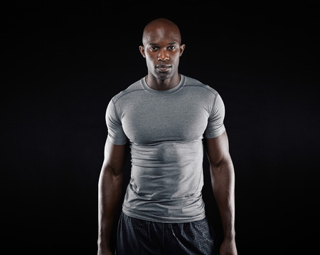 fitness model: Portrait of fit young man with muscular build standing against black background. Afro american fitness model.