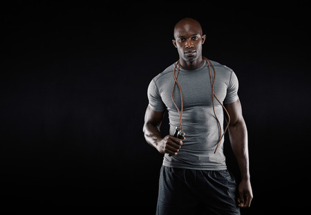 health   fitness: Studio shot of young african muscular man with jumping rope against black background. Fitness model with skipping rope around his neck with copy space.