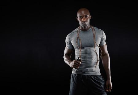 Studio shot van jonge Afrikaanse gespierde man met touwtje springen tegen zwarte achtergrond. Fitness model met een springtouw om zijn nek met een kopie ruimte.