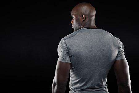 黒の背景に筋肉を構築立ってフィットの若い男の背面します。アフロ アメリカン ジムモデル コピー スペースを見てします。 写真素材