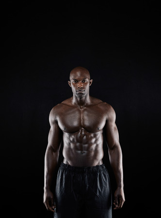 physique: Portrait of a bodybuilder with muscular physique posing against black background. Masculine african fitness model standing shirtless.