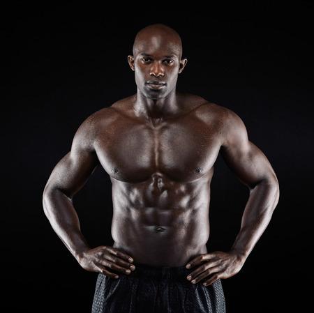 hombre sin camisa: Retrato de un hombre afro-americano fuerte muestra apagado su constitución contra el fondo negro. Modelo masculino descamisado con las manos en las caderas.