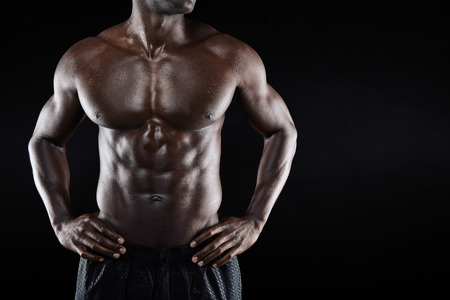 Cropped image of shirtless african man with hands on hip while standing against black background. Close-up of torso of a muscular man with copyspace. Stock Photo