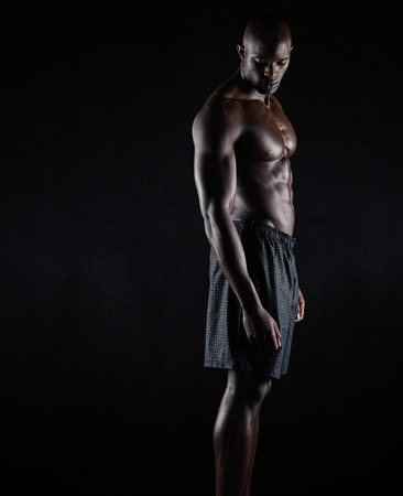 physique: Portrait of a bodybuilder with muscular physique standing against black background. Masculine african fitness model standing shirtless looking down.